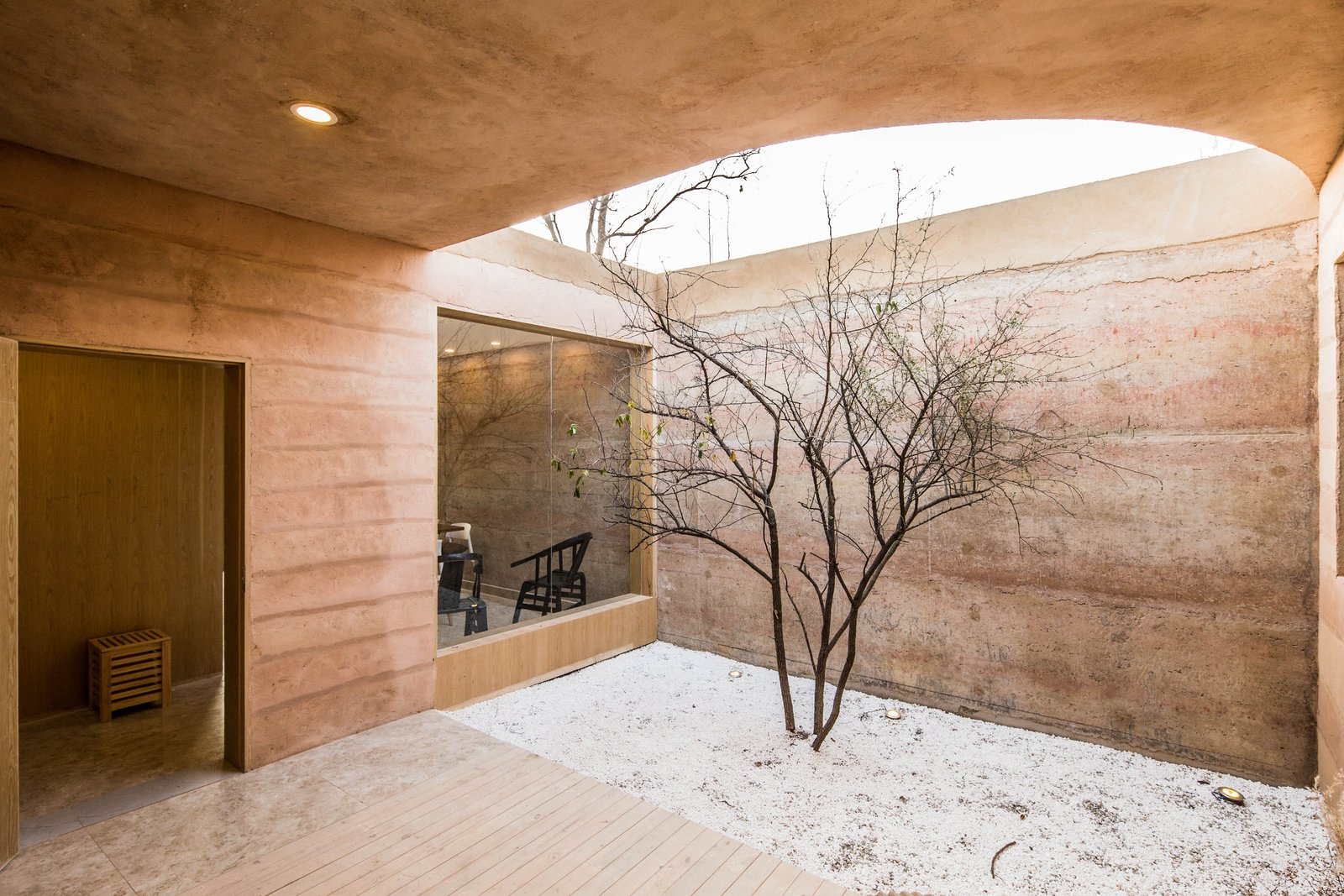 Outdoor, Wood, Trees, Gardens, Hardscapes, Decking, Side Yard, and Back Yard An interior courtyard.  Best Outdoor Gardens Wood Photos from An Old Cave Dwelling in Central China Is Transformed Into a Stylish Home