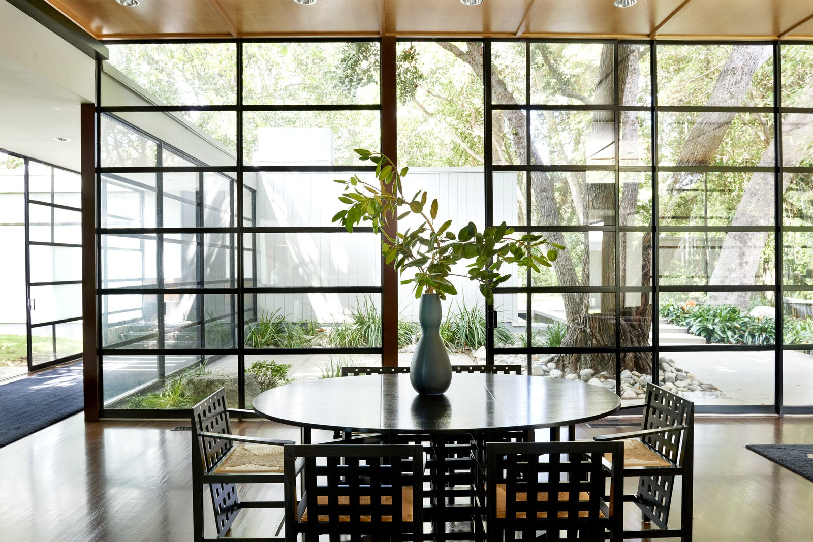 Dining Room, Chair, Table, Medium Hardwood Floor, and Ceiling Lighting The glass wall of windows lets in plenty of natural light.  Photo 5 of 15 in Jerry Bruckheimer Asks $11.9M For This Gem Designed by Thornton Abell