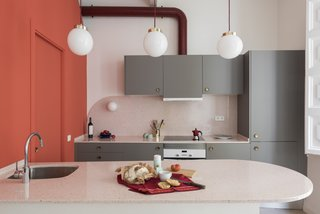 Three globe pendants with brass details and burgundy cords that match the hood tube hang above the kitchen island.
