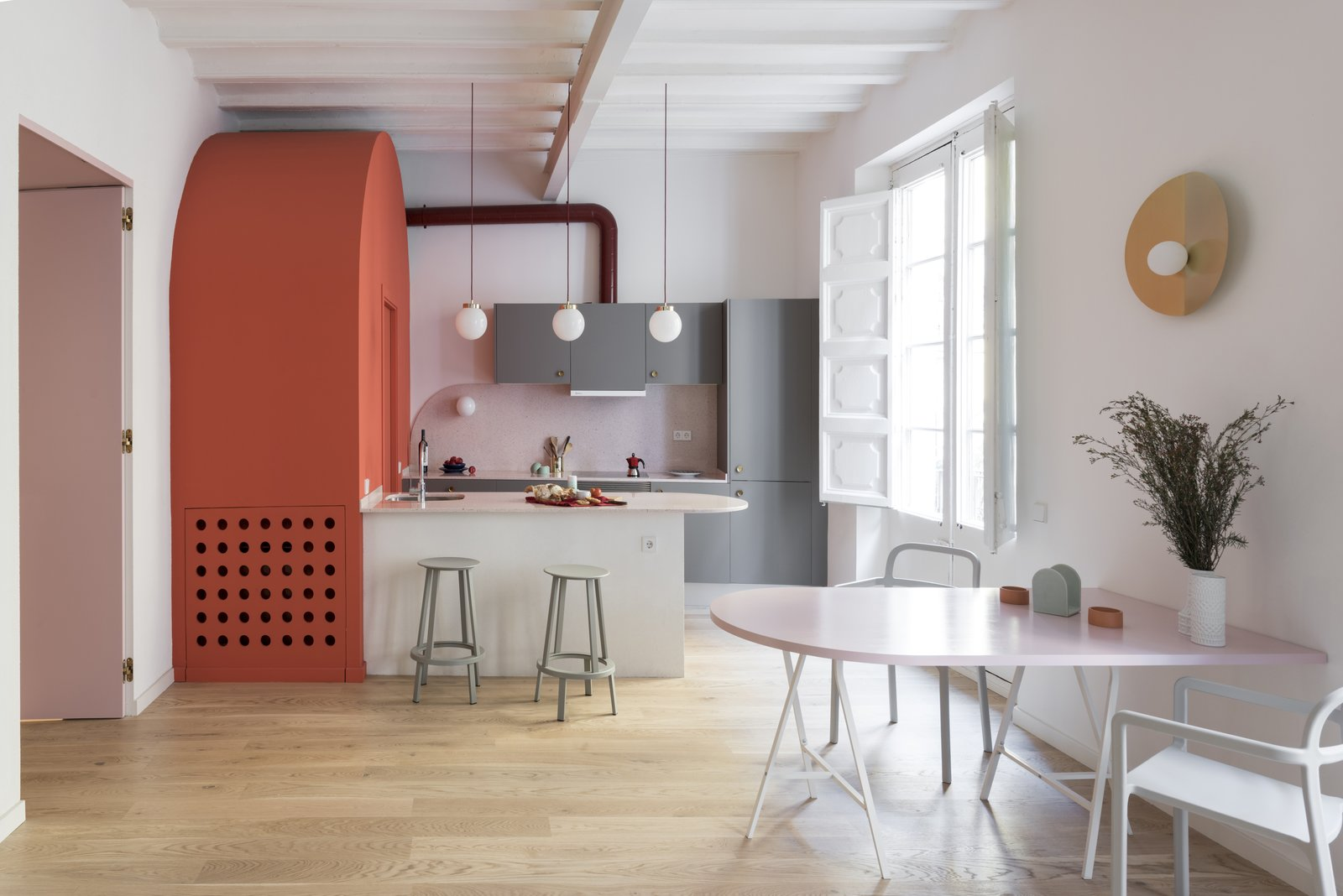 Dining Room, Light Hardwood Floor, Stools, Wall Lighting, Table, Pendant Lighting, and Chair An arc motif is a recurring theme throughout the kitchen's design.  Photos from Before & After: An Ancient Barcelona Apartment Gets a Colorful, Chic Makeover
