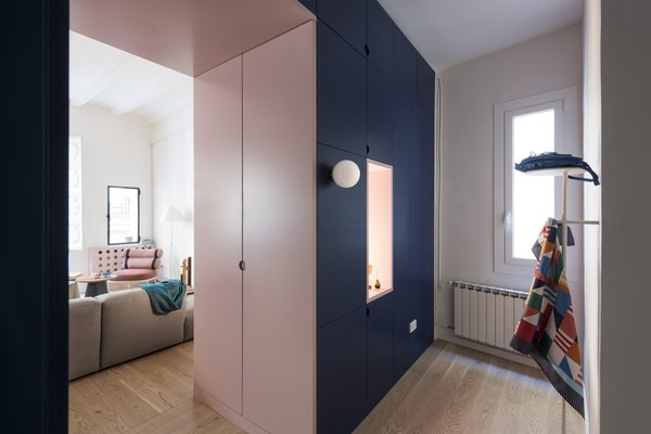 A cut-out, light pink doorway connects the living area to the entrance while hiding closet doors on both sides.