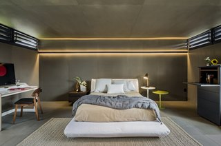 In one of the more unusual bedroom lighting ideas for the ceiling that we've seen, a dramatic backlight illuminates the wall and part of the ceiling in this otherwise dark bedroom.