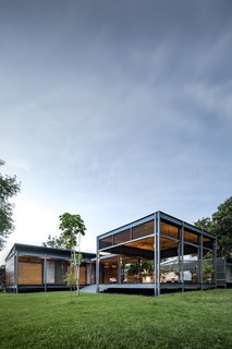 The the warm wood siding is juxtaposed against the industrial grey steel frame of the structure.
