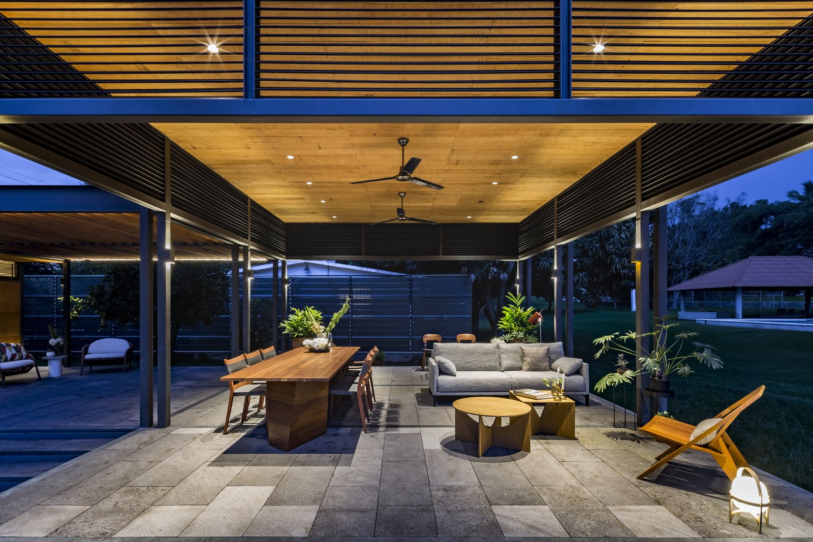Outdoor, Back Yard, Stone, Large, Grass, and Planters The outdoor benefits from ceiling fans to help circulate the air and keep things cool.  Best Outdoor Back Yard Planters Photos from This Modern Prefab Is Now a Gorgeous Guest House