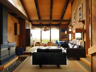 The living room features ample glazing and an exposed beam ceiling.