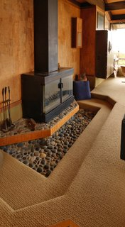 This mini conversation pit is set around a pebble-floored hearth and a steel fireplace. The warm, textured seating area reinforces the fireplace as the central feature of the room.