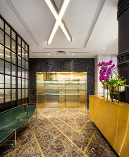 The lobby is a vibrant mix of gold and granite with deep green leather vintage seating.