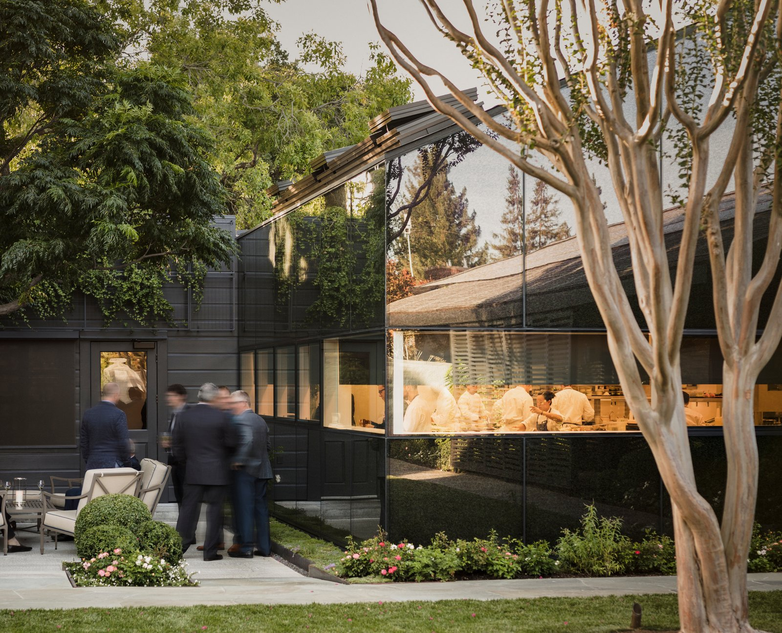 The pitched, low-slung roofs of the kitchen and annex allude to their utilitarian function. Tagged: Exterior, Wood Siding Material, Gable RoofLine, and Glass Siding Material.  Photo 5 of 12 in A Look Inside The French Laundry's Stunning $10M Renovation