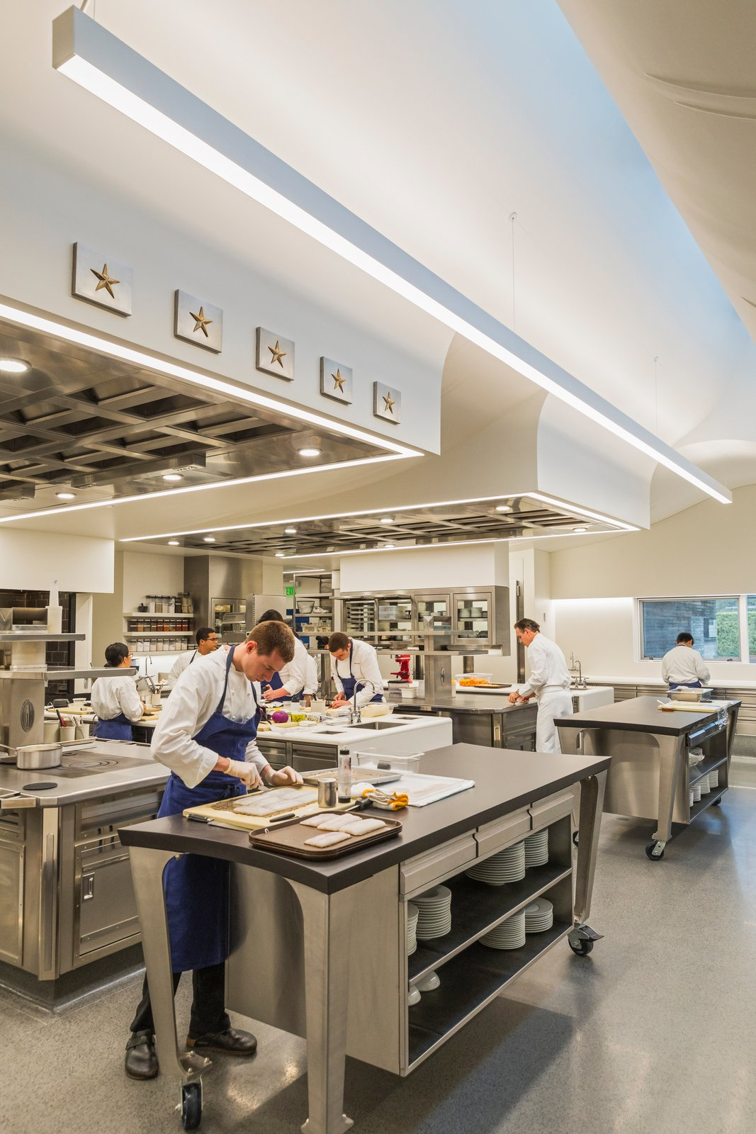 The 2,000-square-foot kitchen provides a comfortable, light-filled working space for the chefs and is configured as a single, continuous space. Tagged: Kitchen, Metal Cabinet, Cooktops, Recessed Lighting, and Terrazzo Floor.  Photo 8 of 12 in A Look Inside The French Laundry's Stunning $10M Renovation