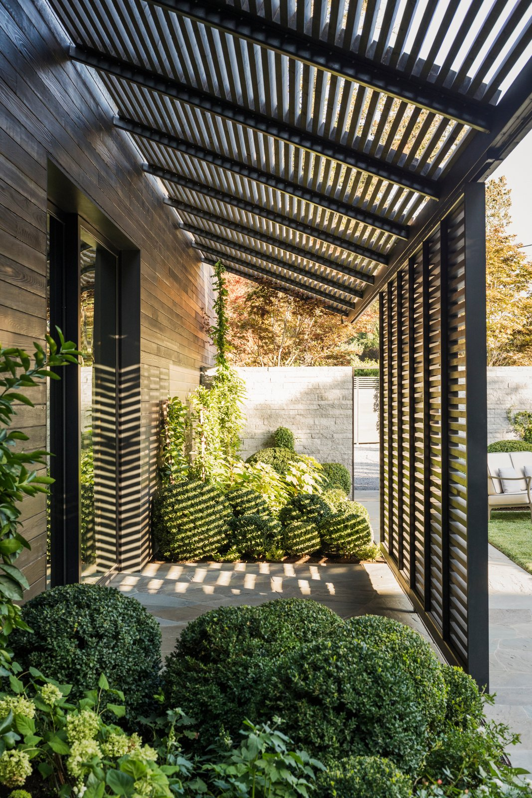 Outdoor, Stone, Walkways, Shrubs, and Front Yard Flush at the corners where the eaves of the roof meet the siding, the kitchen's streamlined body is partly clad in charred wood.  Best Outdoor Stone Front Yard Photos from A Look Inside The French Laundry's Stunning $10M Renovation
