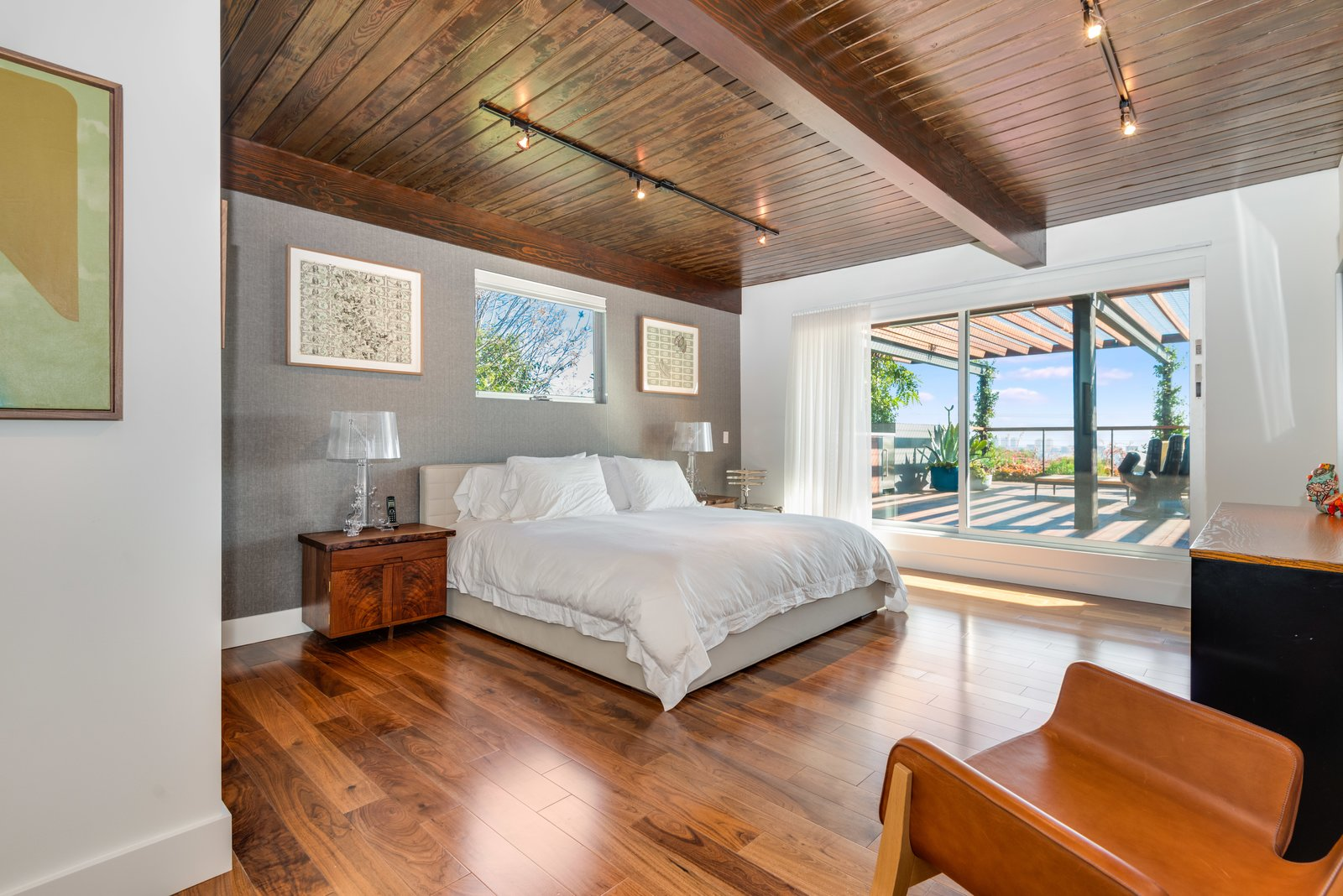 Bedroom, Dresser, Chair, Medium Hardwood, Night Stands, Bed, Table, Lamps, and Track The second bedroom also opens to the terrace and features an ensuite bath.  Best Bedroom Bed Lamps Photos from A Renovated Harry Gesner–Designed Midcentury in L.A. Wants $9.4M