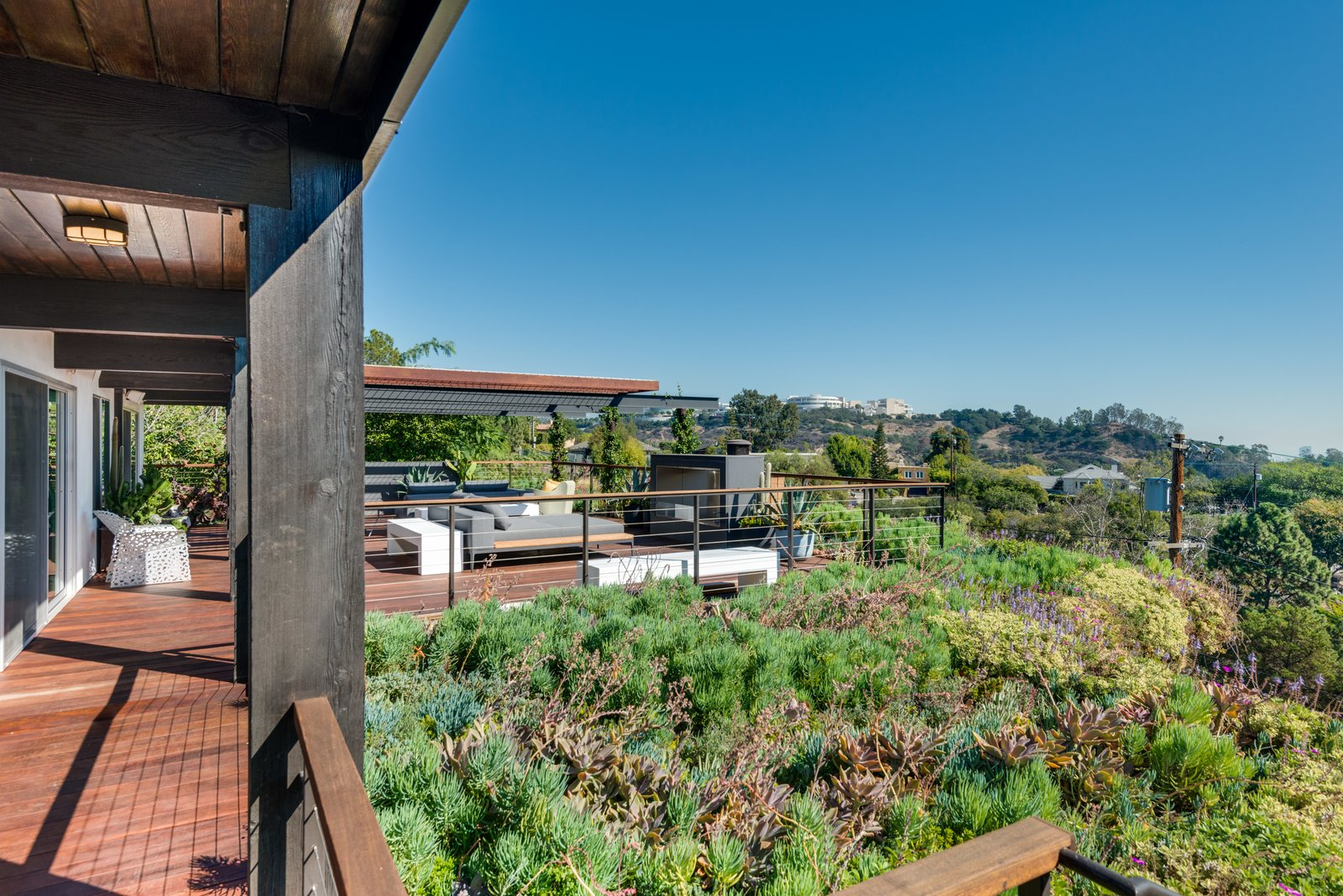 Outdoor, Back Yard, Decking, Metal, Wood, Shrubs, Garden, and Gardens Inspiring views can be had from every angle on the terrace.  Best Outdoor Shrubs Metal Photos from A Renovated Harry Gesner–Designed Midcentury in L.A. Wants $9.4M