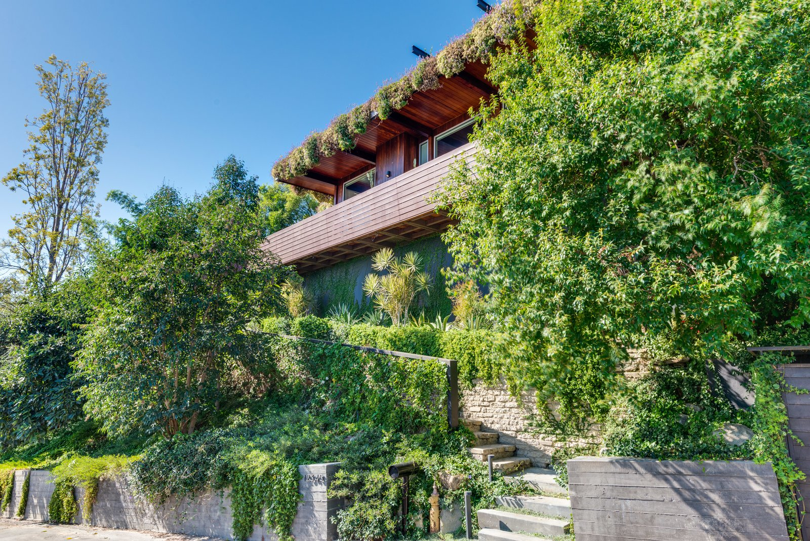 Exterior, Wood, House, Flat, Concrete, Brick, Mid-Century, and Green The outdoor spaces and roof deck are impressive and feature a living roof succulent garden.  Best Exterior Brick Concrete Photos from A Renovated Harry Gesner–Designed Midcentury in L.A. Wants $9.4M