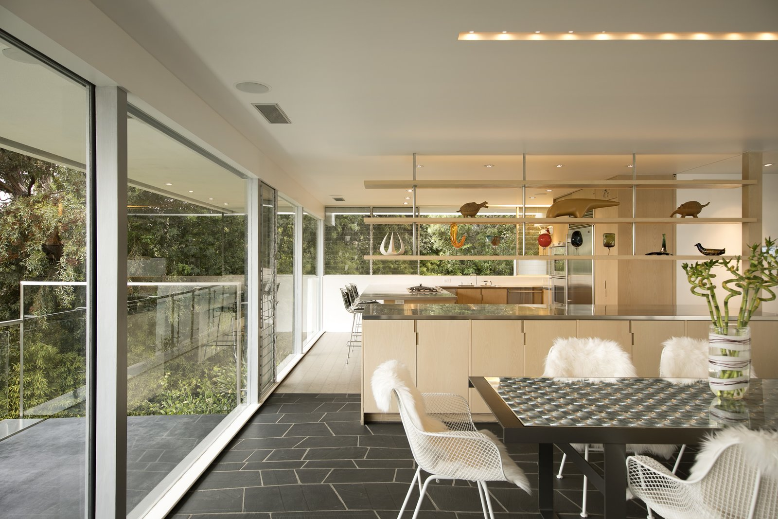 Dining Room, Slate Floor, Chair, Recessed Lighting, and Table Ash cabinetry and stainless steel appliances in the kitchen and living room.  Photos from A Restored Midcentury Jewel by Richard Neutra Hits the Market at $13.5M