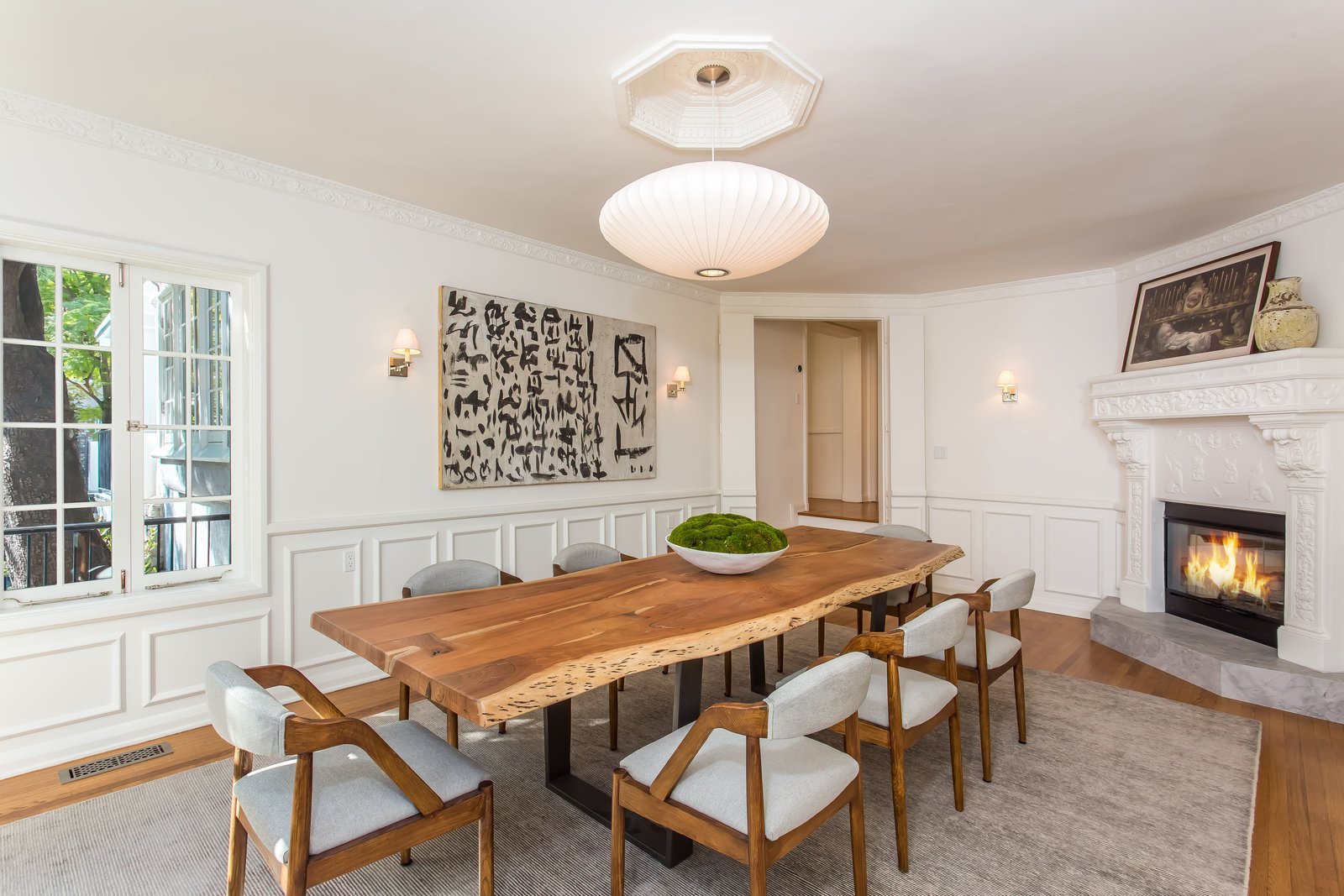 Dining, Table, Accent, Chair, Medium Hardwood, Wall, and Corner Another intricately detailed wood-burning fireplace graces the dining room.  Best Dining Accent Wall Photos from Moby Lists His Newly Renovated Los Feliz Manor For $4.5M