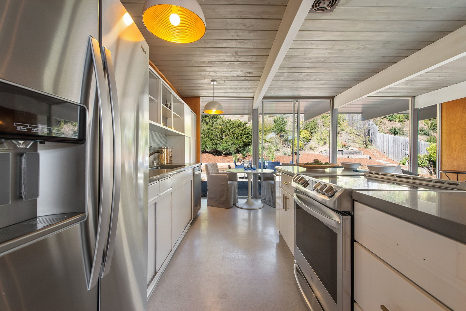 Kitchen, White Cabinet, Refrigerator, Cooktops, Wall Oven, Pendant Lighting, Drop In Sink, and Glass Tile Backsplashe Appliances have been updated in keeping with the design.  Photo 8 of 21 in An Elegant Eichler Hits the Market at $1.15M in Northern California
