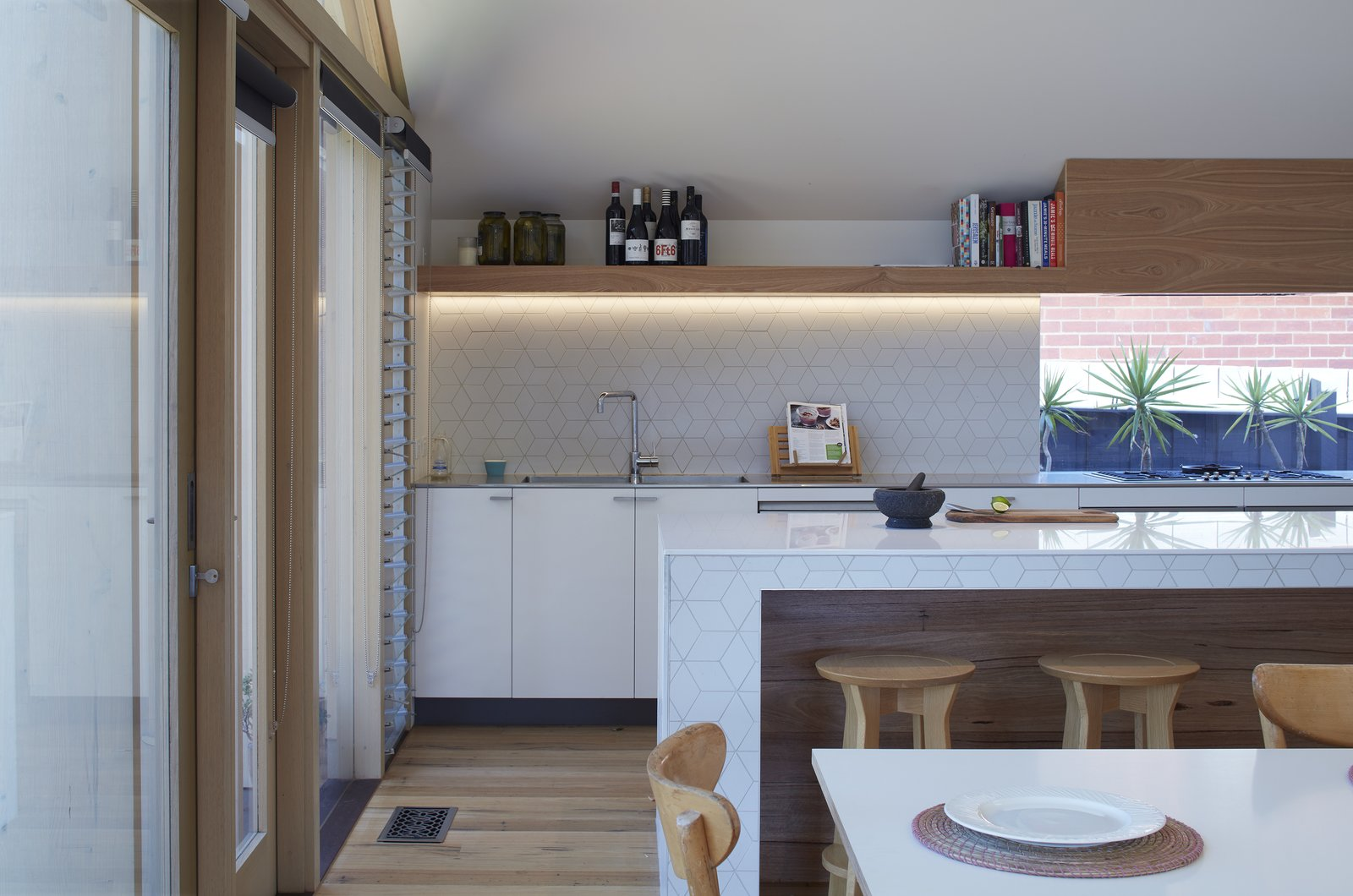Kitchen, White, Porcelain Tile, Medium Hardwood, Drop In, Wood, Cooktops, and Accent The extension created an open kitchen as well as additional interior space for dining and living.  Best Kitchen Wood Drop In Accent Photos from A Contemporary Extension Gives This Australian Home a New Face