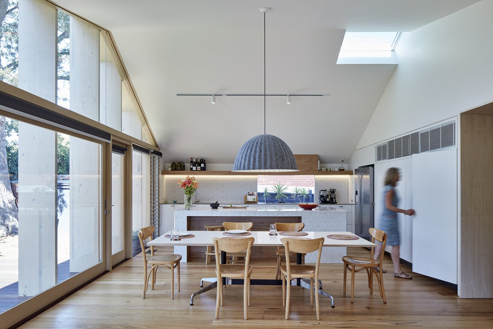 Dining Room, Medium Hardwood Floor, Table, Chair, Pendant Lighting, and Track Lighting Strategically placed openings and an automated roof window at the apex of the slanted ceiling can be opened to release hot air during the summer months.  Best Photos from A Contemporary Extension Gives This Australian Home a New Face