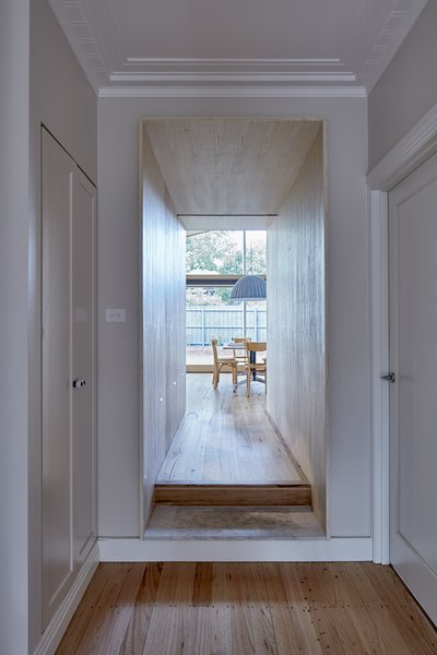 """Spatial interconnectivity is facilitated through a plywood """"chute"""" that connects and delineates the original house from the new addition."""