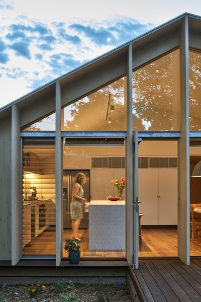 Floor-to-ceiling glass with sliding glass doors allow access to the decked outdoor space, covered by the roof's overhang.