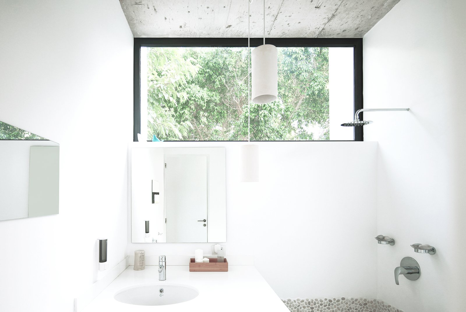 Bath Room, Pendant Lighting, Concrete Wall, Open Shower, and Undermount Sink The bathroom maintains a sense of outdoor living with the large clerestory window.  Photo 9 of 14 in Rent This Modular Micro Cabin For Your Next Grecian Getaway
