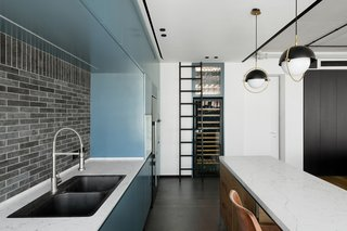 Theblack and white color scheme uses a cool share of teal as an accent color in the kitchen.