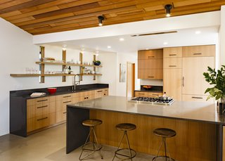 The kitchen had been remodeled in the 80s and had an unfortunate layout. JHL Design revised the layout using an open kitchen concept and adding an eat-in bar. The redesign also brought back some of the original windows from the front of the house that peeked into the kitchen and modernized it by hanging shelves over the window for convenience and architectural interest. Oregon White oak was used for the cabinet faces and the countertop is quartz.