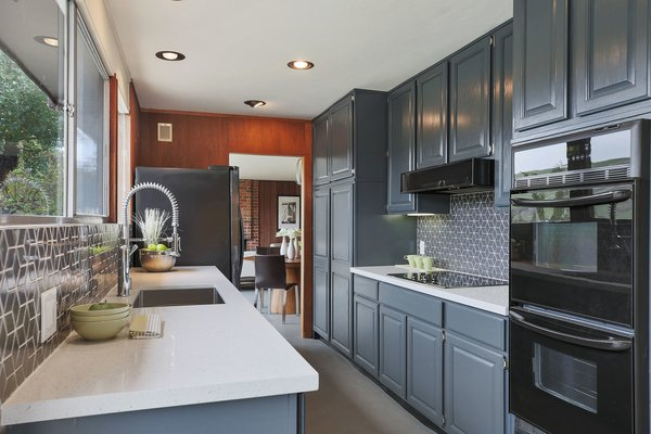 The updated kitchen features new quartz stone countertops, a tiled backsplash, and new stainless steel appliances.