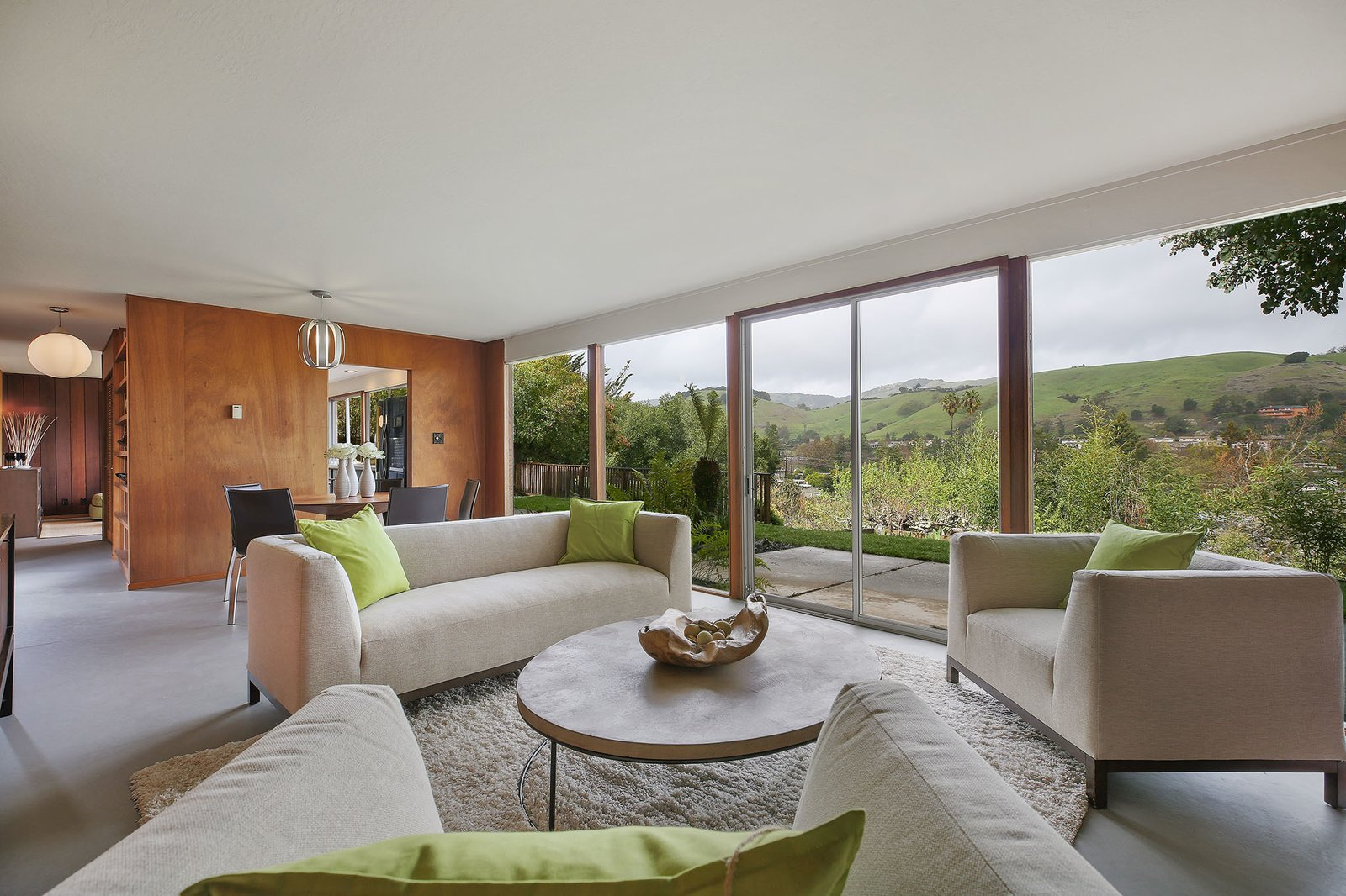 Living Room, Sofa, Chair, Coffee Tables, Concrete Floor, Rug Floor, and Pendant Lighting The wall of glass brings in a strong connection to the outdoors.  Photo 5 of 15 in This Rare Two-Story Eichler Has Just Been Listed For $1.35M