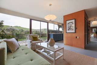 The family room has floor-to-ceiling windows which overlook the surrounding hilly landscape.