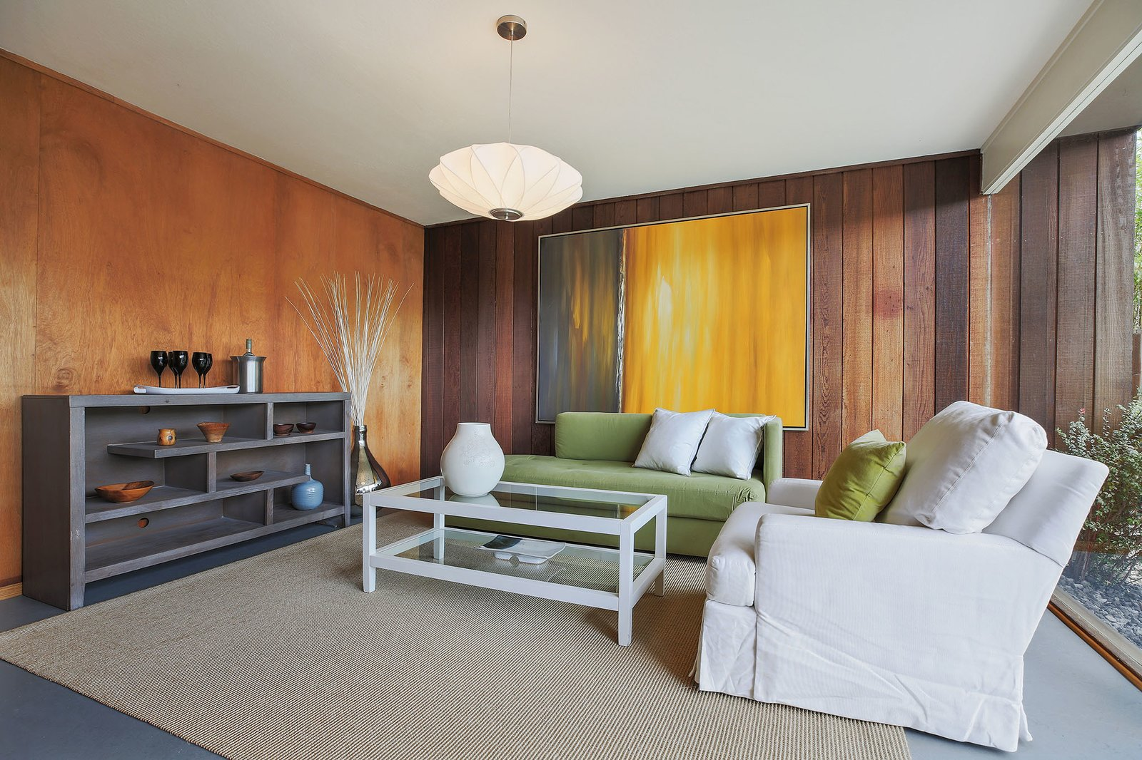 Living Room, Sofa, Bookcase, Chair, Pendant Lighting, Rug Floor, and Coffee Tables Original details including mahogany and redwood walls.  Photo 10 of 15 in This Rare Two-Story Eichler Has Just Been Listed For $1.35M