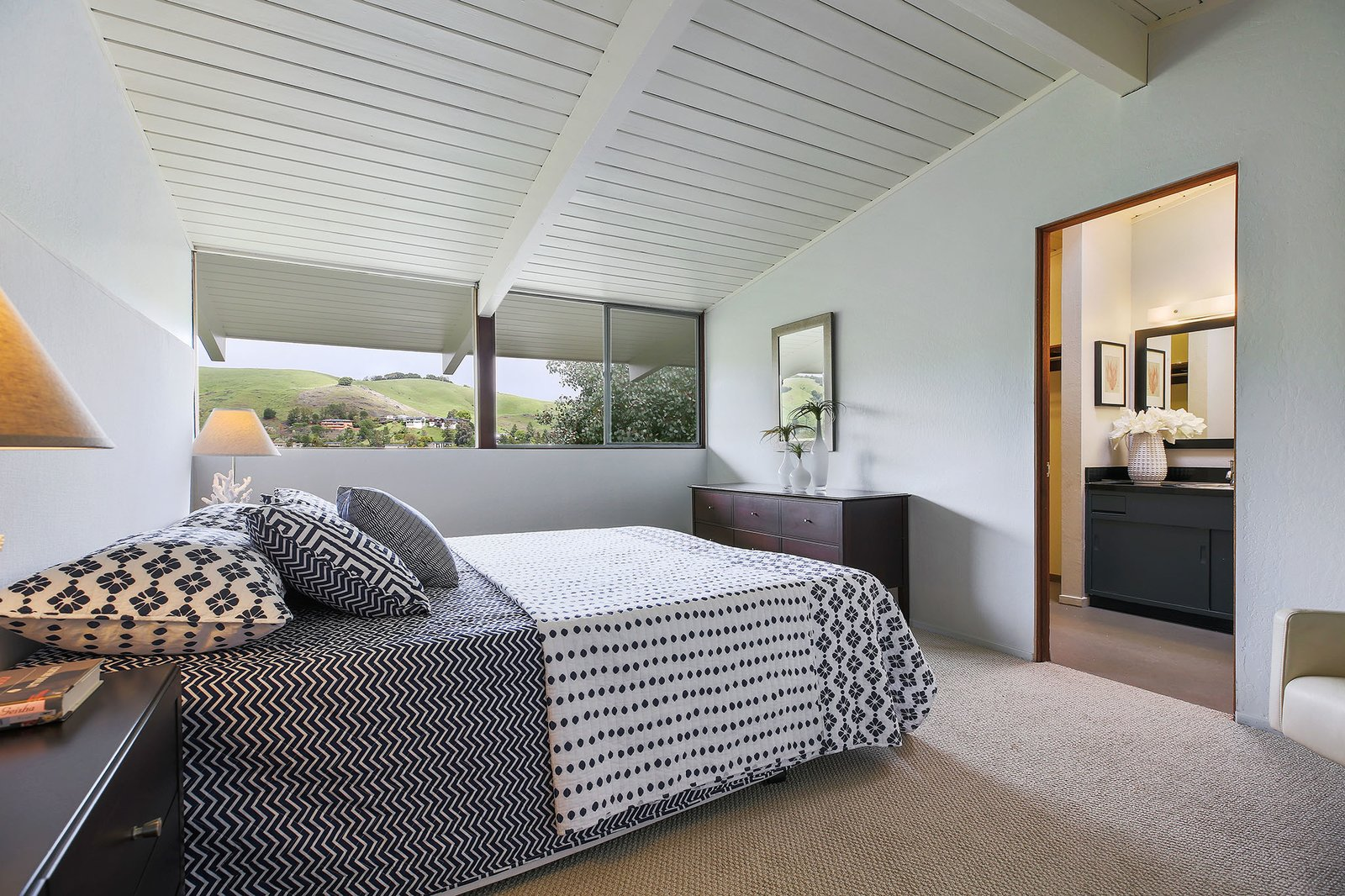 Bedroom, Dresser, Bed, Table Lighting, Carpet Floor, Lamps, and Night Stands The master bedroom has an en-suite bathroom and a large walk in closet.  Photo 12 of 15 in This Rare Two-Story Eichler Has Just Been Listed For $1.35M