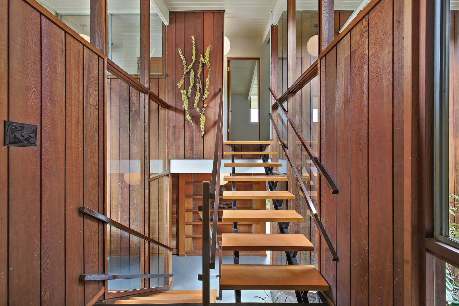 Staircase, Wood Railing, and Wood Tread The floating staircase gives  Photo 3 of 15 in This Rare Two-Story Eichler Has Just Been Listed For $1.35M