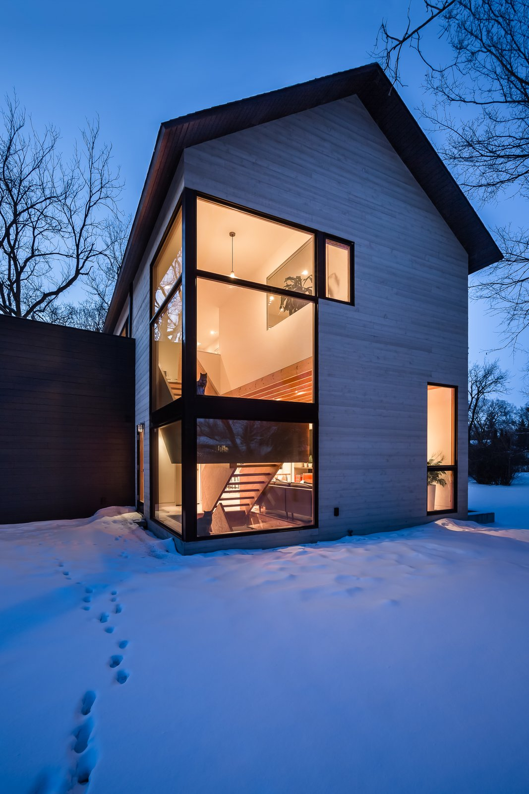 Exterior, Flat RoofLine, House Building Type, Wood Siding Material, and Gable RoofLine Large-scale picture windows help bring as much natural light into the home as possible.  Photo 5 of 13 in An Intern Architect Builds a Home For His Growing Family on a Strict Budget