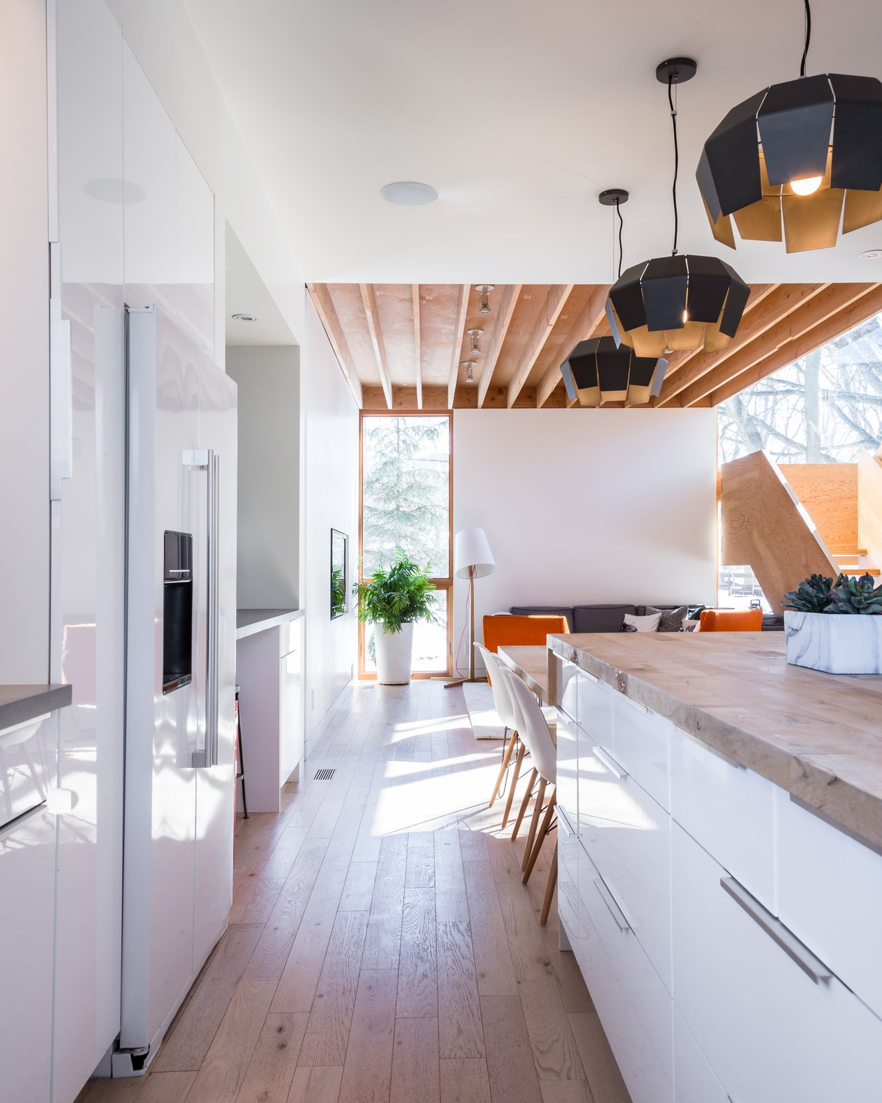 Kitchen, Refrigerator, White Cabinet, Pendant Lighting, Medium Hardwood Floor, and Wood Counter The dimensions of the table were based on the amount of wood that could be salvaged from the tree.  Photo 11 of 13 in An Intern Architect Builds a Home For His Growing Family on a Strict Budget