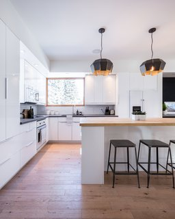 The open plan of this white kitchen helps keep the interiors bright, while also creating a greater sense of spaciousness. The black stools at the bar draw the eye upward to the unique black light fixtures in this white kitchen with black countertops.