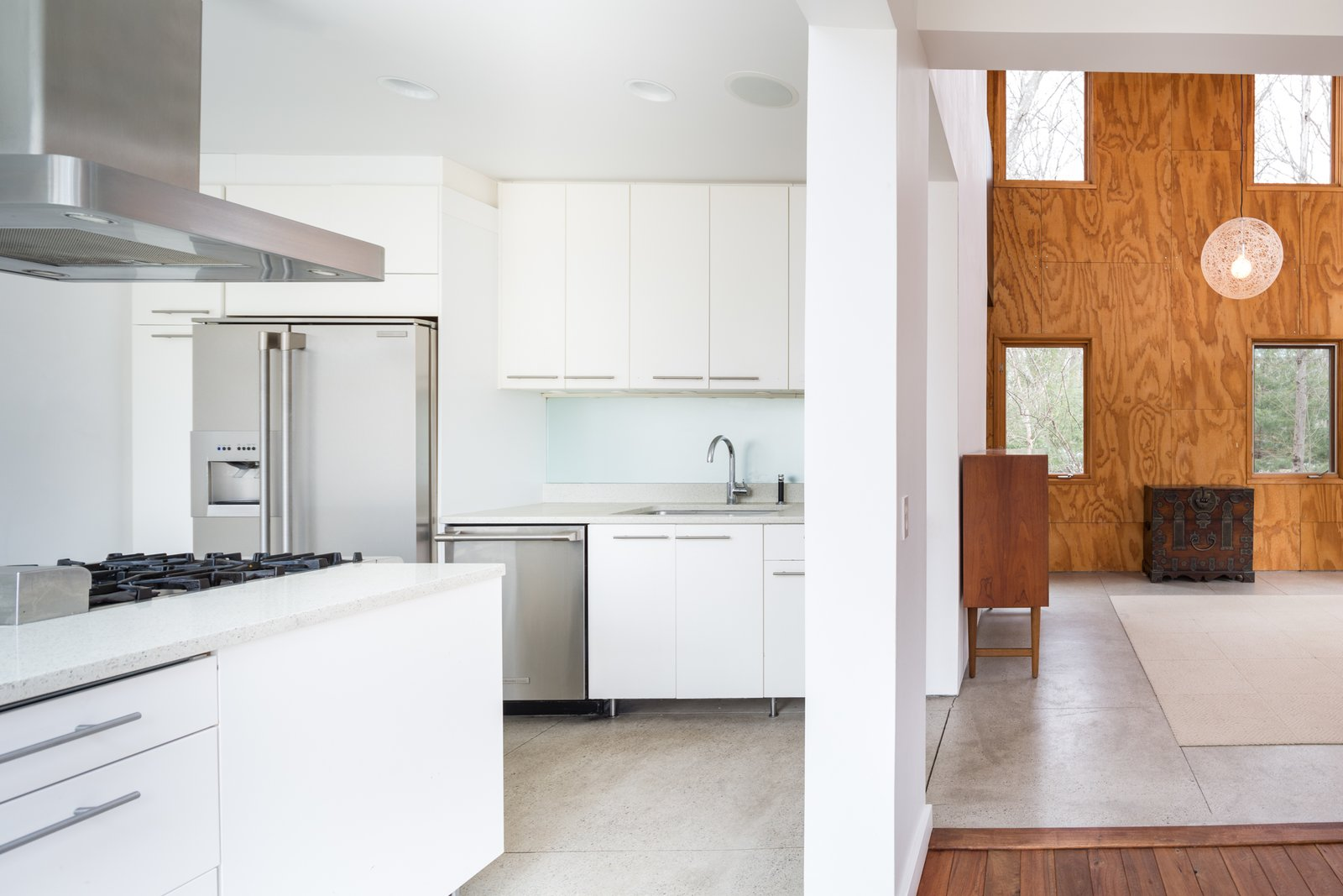 The double-height living area features unfinished plywood cladding. The sleek, contemporary kitchen features a center island, as well as stainless steel appliances.