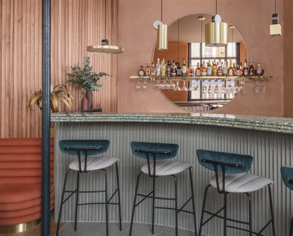 Assorted brass pendant lighting over the terrazzo bar.