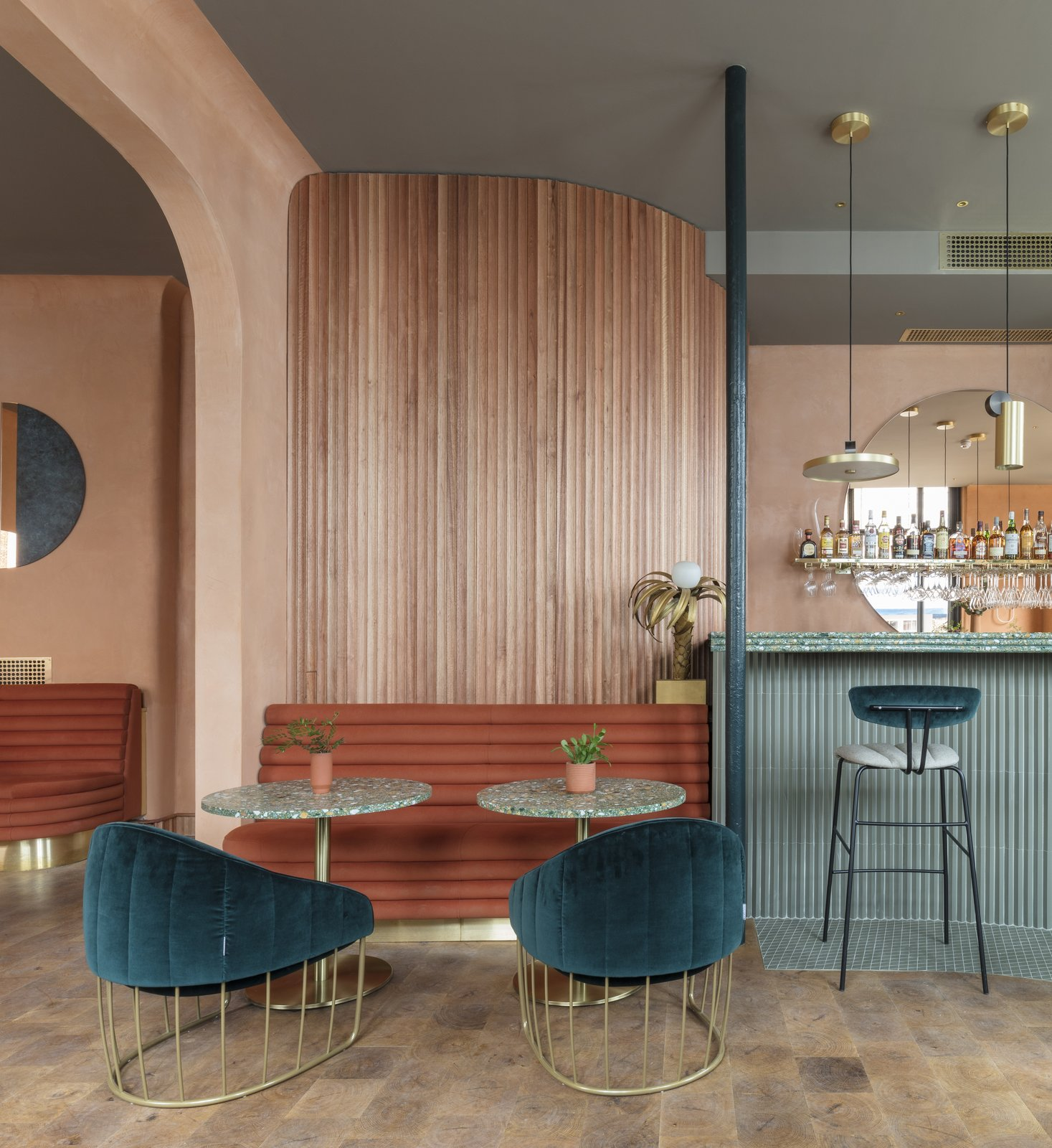Scalloped Sapele wood slats on the walls add a textural organic element—the tubular design a running motif in the design.