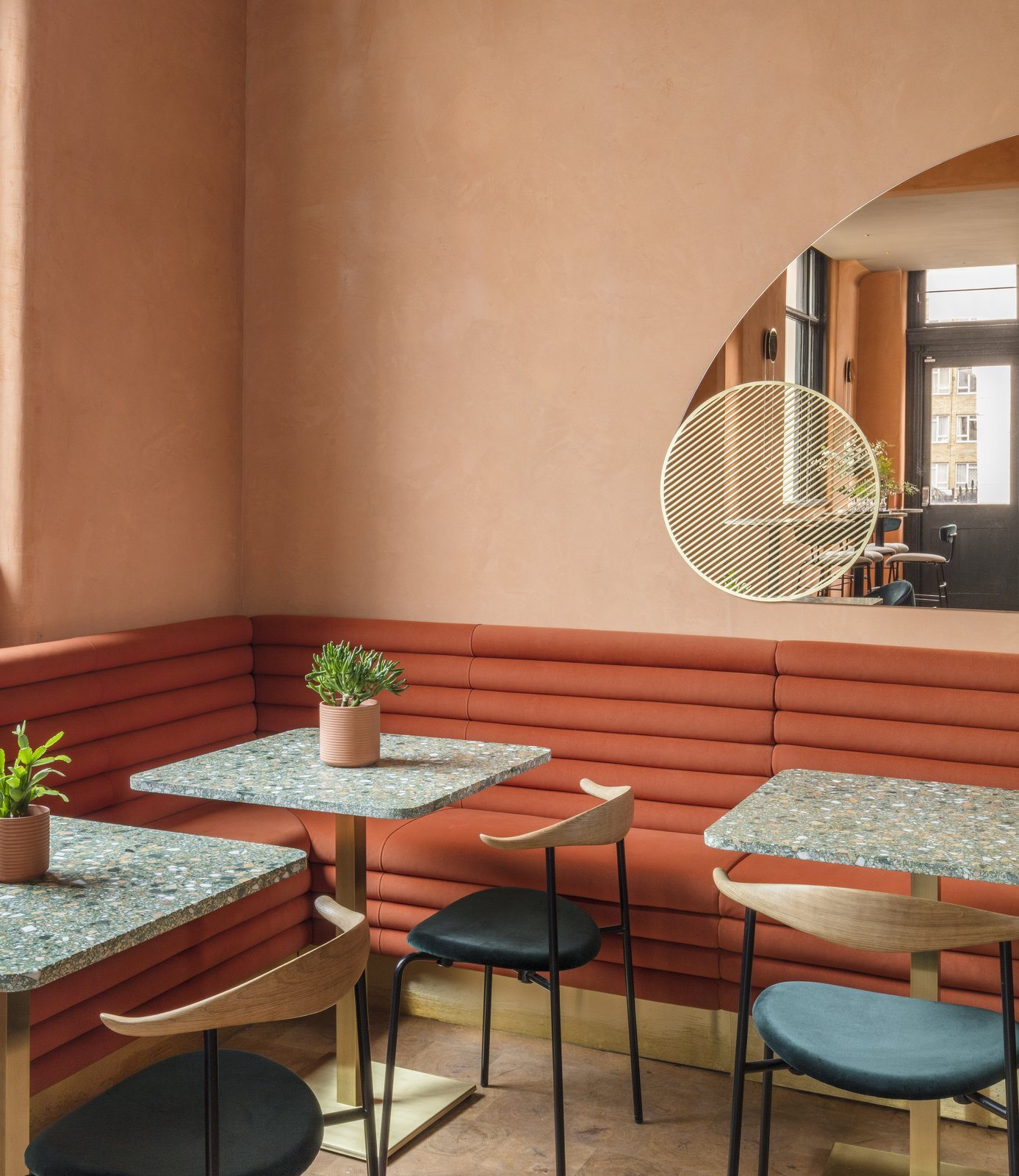 Custom-made rust-colored tubular suede banquettes accentuate the sunny color-palette.