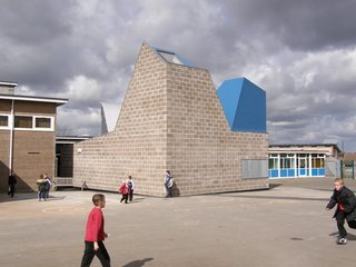 Built out of raw concrete blocks, the building's interior is finished with bare plywood, OSB, and a varnished concrete screed.