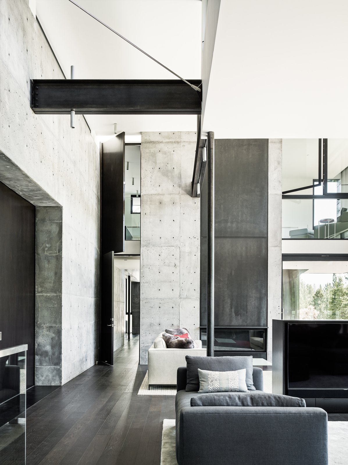 Living Room, Dark Hardwood Floor, Bench, Sofa, Standard Layout Fireplace, Ceiling Lighting, Rug Floor, and Coffee Tables The interior also features a layering of space that can be seen here in the living room.     Photo 7 of 18 in This Concrete Abode Stretches Over Giant Boulders