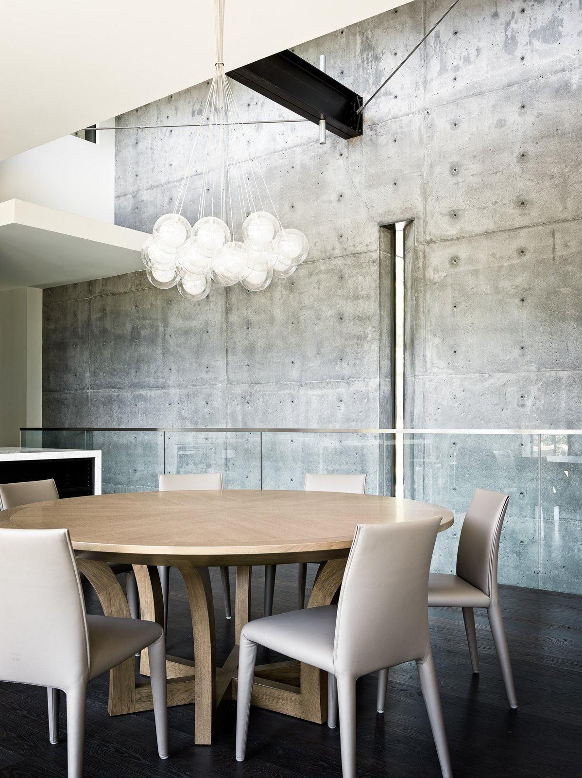 Dining Room, Dark Hardwood Floor, Pendant Lighting, Chair, and Table The interior concrete walls echo the ones on the exterior.    Photo 8 of 18 in This Concrete Abode Stretches Over Giant Boulders