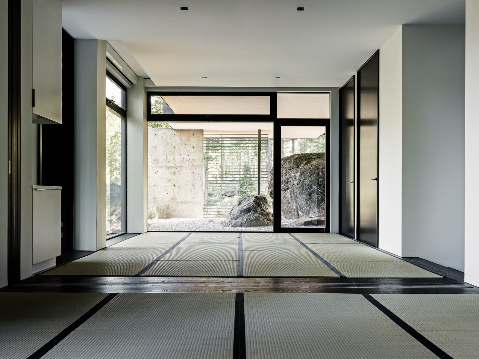 Living Room, Recessed Lighting, and Dark Hardwood Floor A sense of Japanese minimalist design permeates the home. Tatami mats are now used in a space that leads out to a very zen-like rock garden.     Photo 10 of 18 in This Concrete Abode Stretches Over Giant Boulders