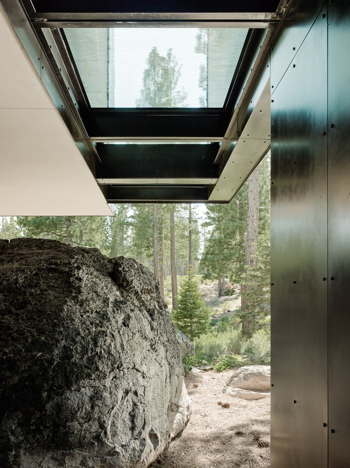 Outdoor, Boulders, Side Yard, and Trees The home cantilevers out over a giant boulder which was originally found on the site and incorporated into the design.     Photo 11 of 18 in This Concrete Abode Stretches Over Giant Boulders