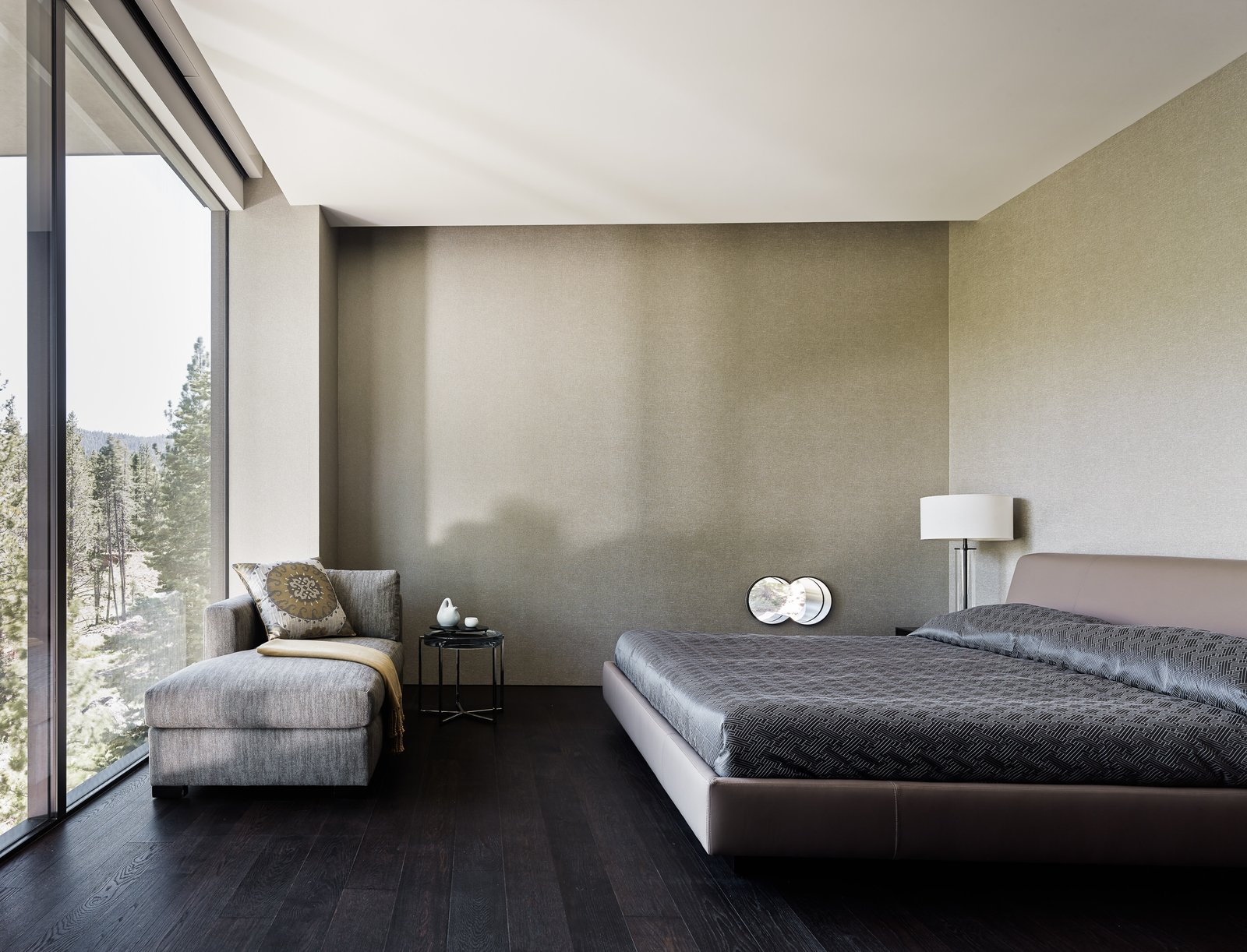 Bedroom, Bed, Table Lighting, Dark Hardwood Floor, and Chair One of the home's bedrooms.  Photo 14 of 18 in This Concrete Abode Stretches Over Giant Boulders