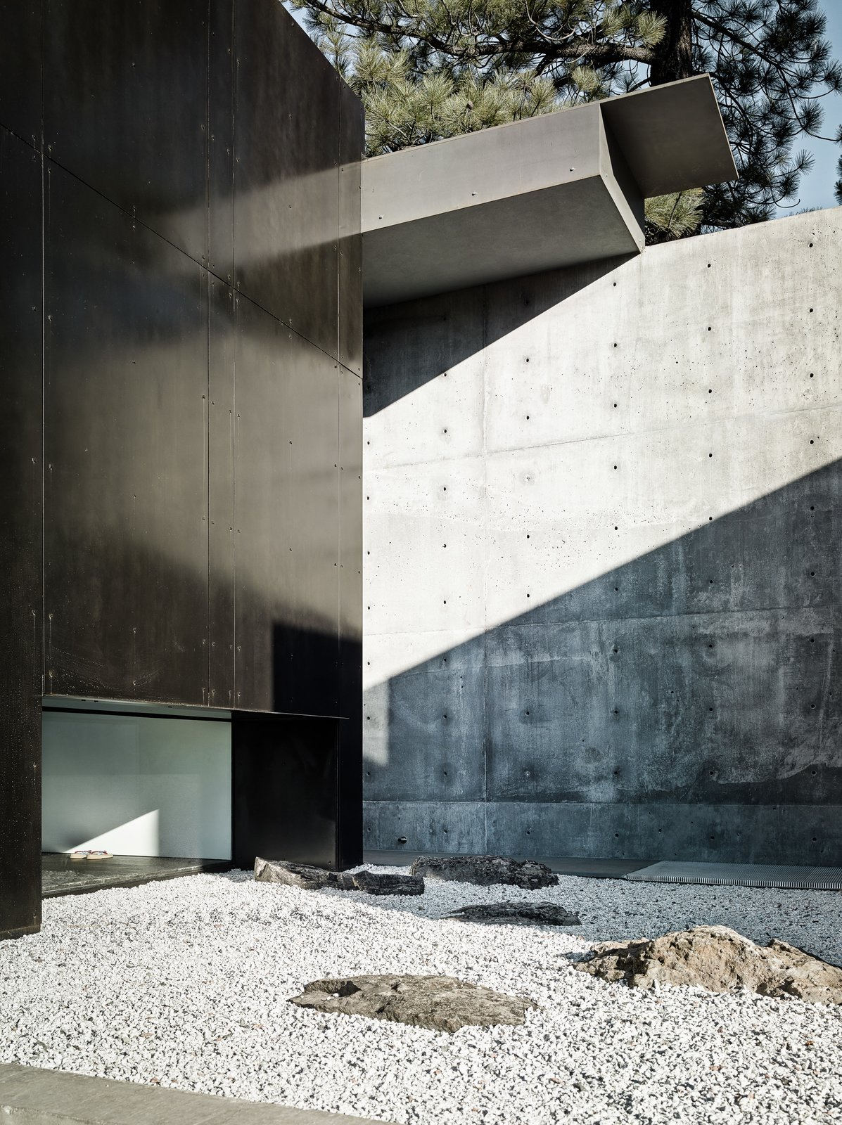 Outdoor, Concrete Fences, Wall, Side Yard, Hardscapes, and Trees The exterior features a poetic layering of spaces that highlights the interplay of light and dark.     Photo 5 of 18 in This Concrete Abode Stretches Over Giant Boulders