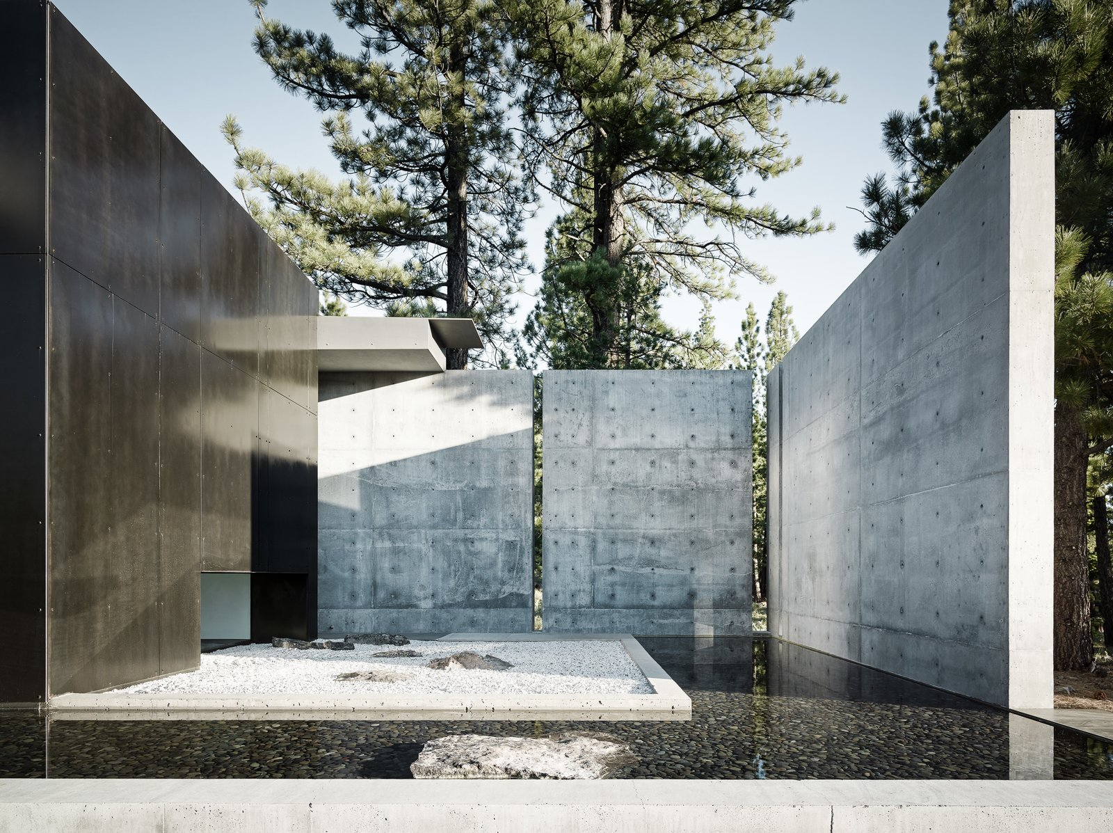 Outdoor, Concrete Fences, Wall, Trees, Side Yard, and Hardscapes Large concrete walls provide both privacy and shade.  Photo 3 of 18 in This Concrete Abode Stretches Over Giant Boulders