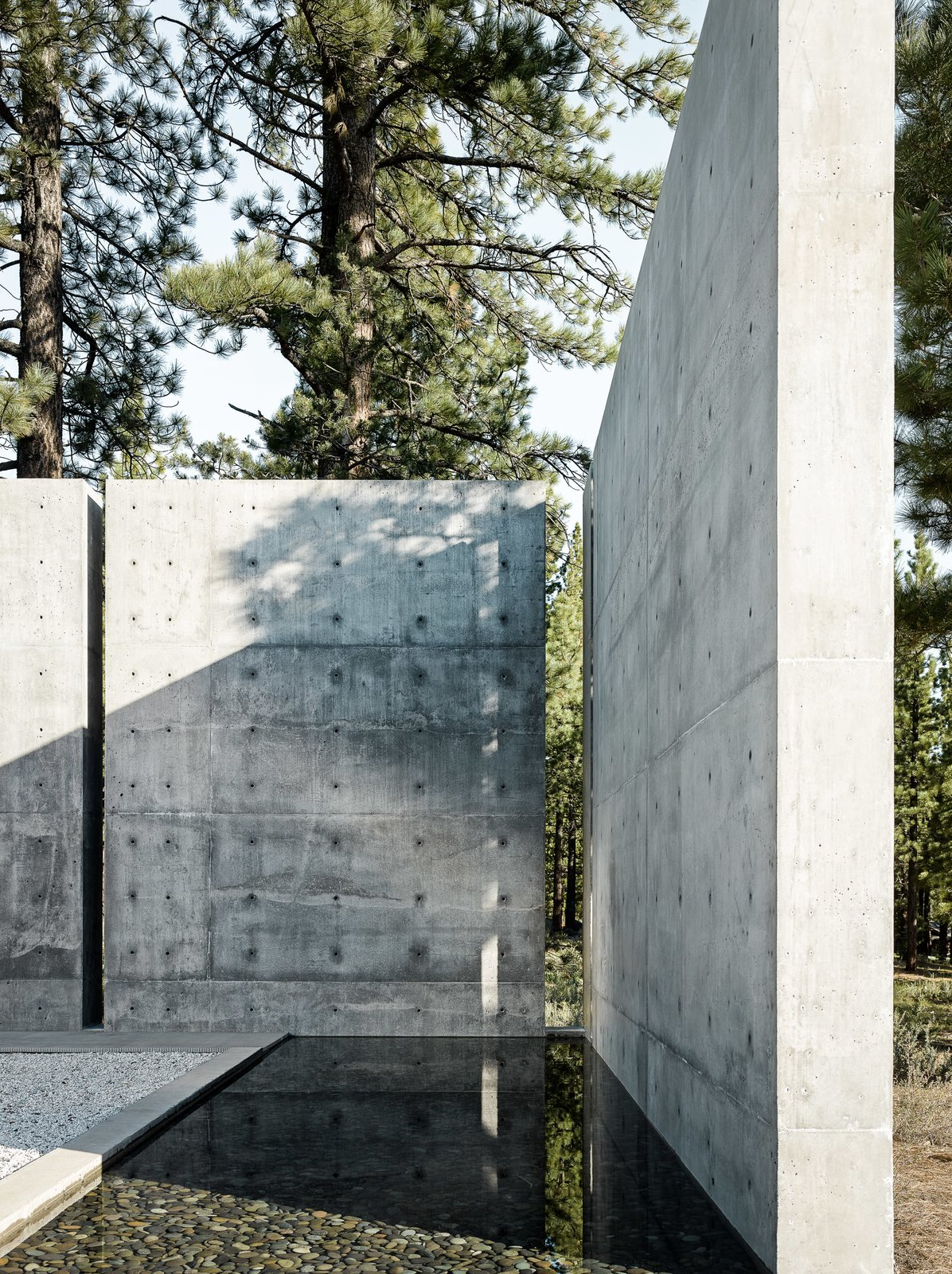 Outdoor, Side Yard, Concrete Fences, Wall, Trees, and Hardscapes The client requested the design to include a water feature. Instead of a pool that would require tremendous upkeep, the architect was inspired by a pool he saw in Spain to produce a rain channel that is fed by rain and melting snow with a valve that the client can easily control.  Photo 4 of 18 in This Concrete Abode Stretches Over Giant Boulders