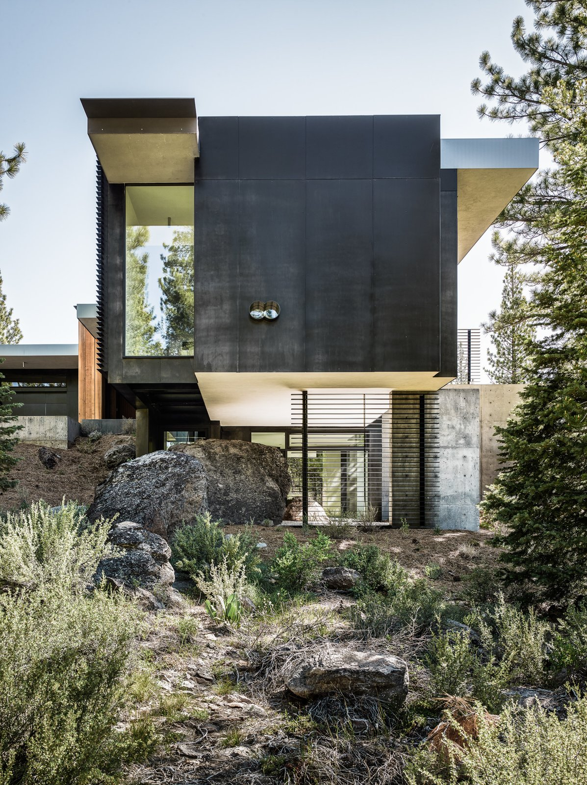 Exterior, Flat RoofLine, Concrete Siding Material, House Building Type, and Metal Siding Material Throughout the site, the original bolders that have been left untouched are evident as the home engulfs them into its design.  Photos from This Concrete Abode Stretches Over Giant Boulders
